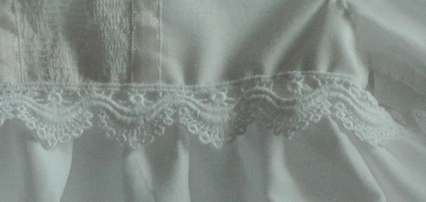 closeup view of lace sewn to lower edge of bodice