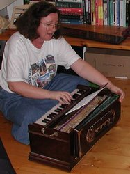 Susan Kramer playing the harmonium for kirtan